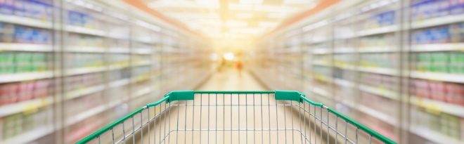 Shopping cart with supermarket aisle blur background